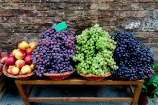 Grapes and nectarines on a bench at a Siena market.